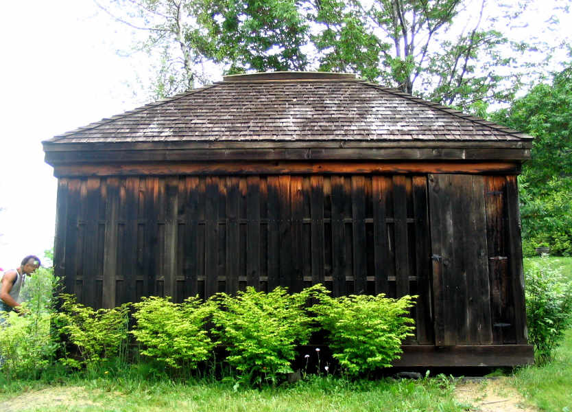 Small wood building with black weather stains.